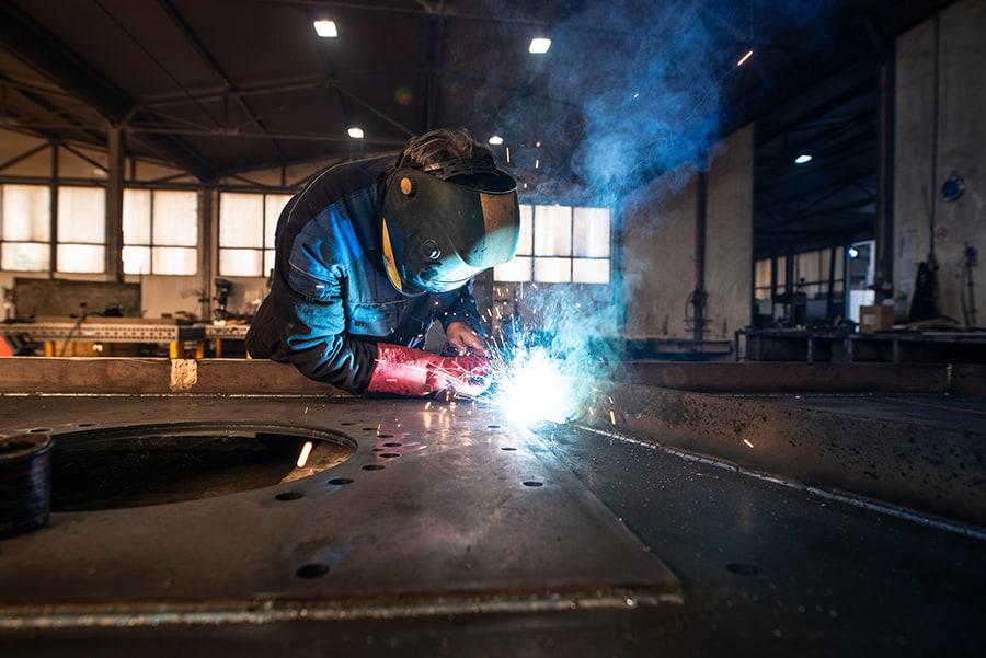 Professional industrial welder welding metal parts in metalworking factory