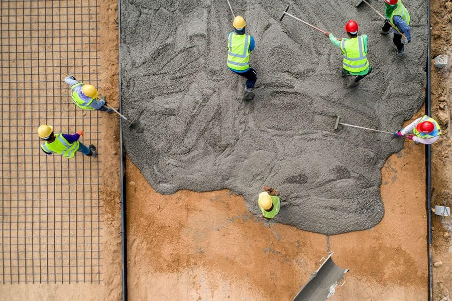 construction workers pouring wet concrete