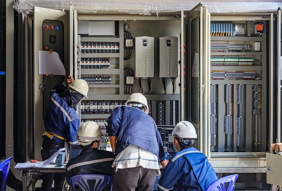 engineers working and checking plc cabinet wiring